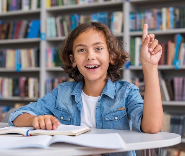 Маленький мальчик, вид спереди, делает домашнее задание в библиотеке