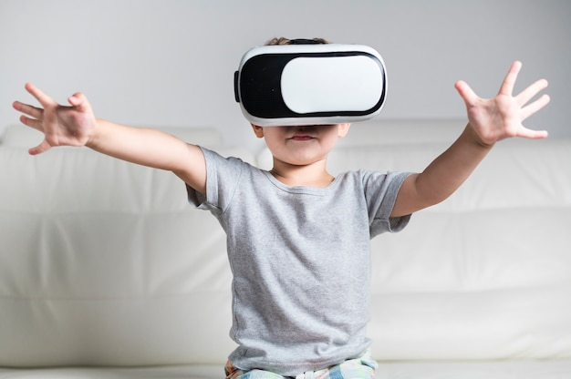 Front view little boy enjoying a pair of vr headset