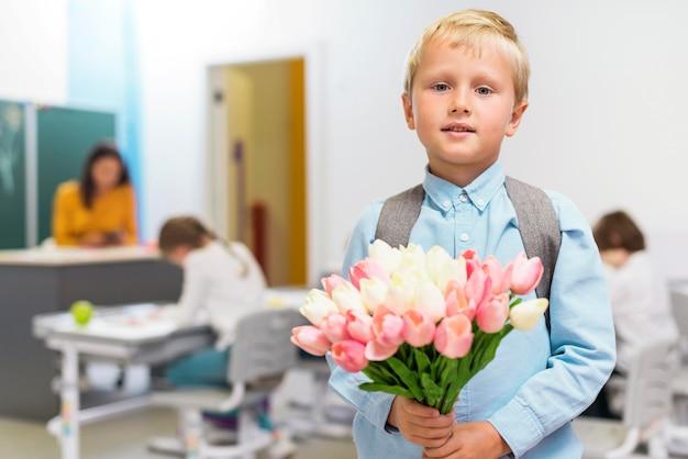 正面に彼の先生のための花の花束を保持している小さな男の子