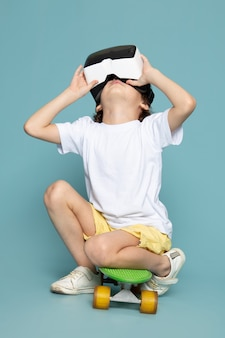 A front view little boy playing vr on the blue space