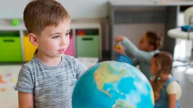 Вид спереди маленький мальчик играет с земным шаром