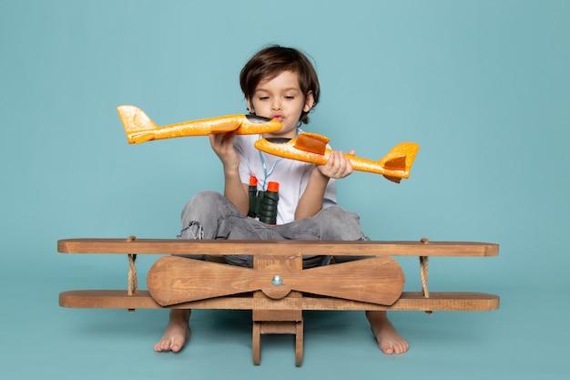 正面の青い床におもちゃの飛行機で遊ぶ少年