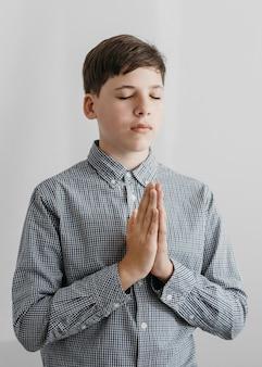 Вид спереди маленький мальчик молится