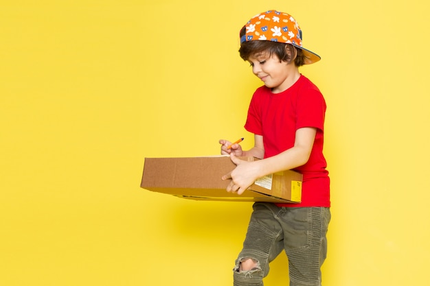 A front view little boy in red t-shirt colorful cap and khaki trousers holding box on the yellow background