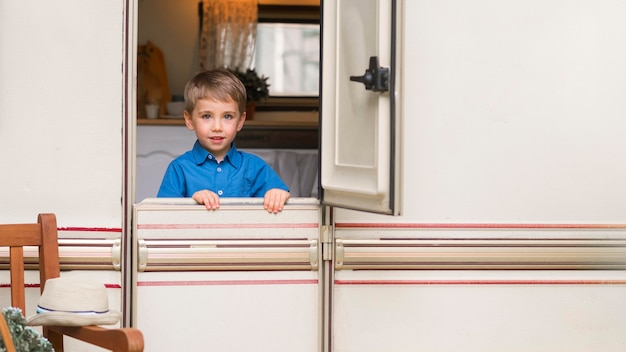 キャラバンのドアの前に立っている少年の正面図