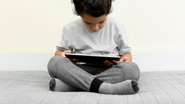 Front view of little boy using tablet in bed