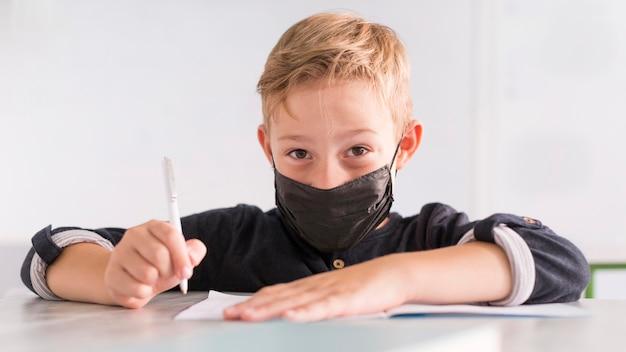 正面に黒い医療マスクを身に着けている男の子