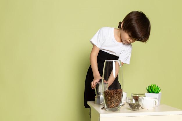Un ragazzino di vista frontale in maglietta bianca che prepara la bevanda del caffè sullo scrittorio color pietra