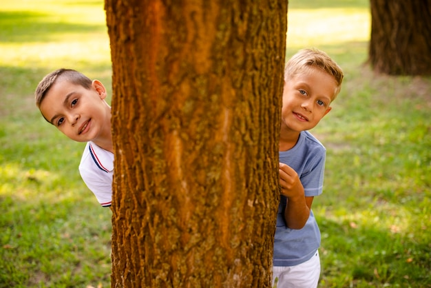 Front view little boys posing behind a tree