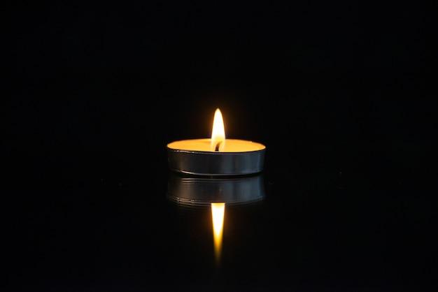 Vista frontale della piccola candela accesa sul nero
