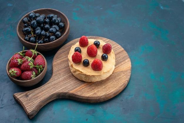 正面図紺色の表面に新鮮なイチゴを使って丸く焼き上げた小さなケーキケーキ焼き甘い砂糖生地のパイ