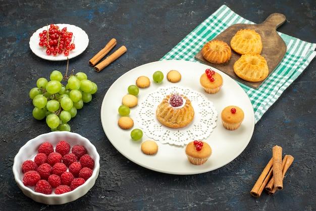 暗いデスク甘いクリームクッキーと緑ブドウラズベリーとクランベリーと正面の小さなケーキ