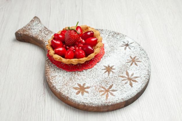 白い机の上の新鮮な果物と正面図の小さなケーキケーキデザートフルーツティー