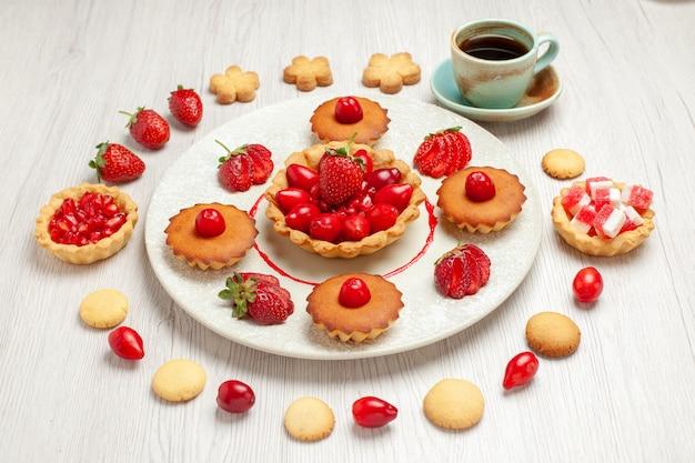 正面図白い机の上の果物とお茶の小さなケーキ果物のデザートケーキ