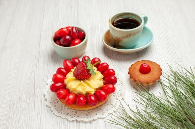 Vista frontale piccola torta con frutta e tazza di tè su scrivania bianca frutta dessert colore tè
