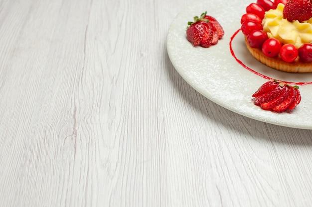 白い机の上のプレートの中に果物が入った正面図の小さなケーキケーキデザートフルーツ