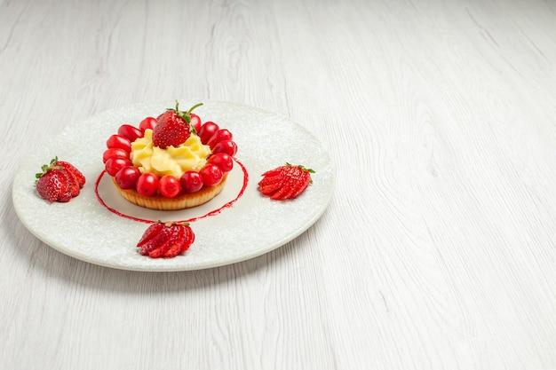 Вид спереди маленький торт с фруктами внутри тарелки на белом столе торт десерт фрукты