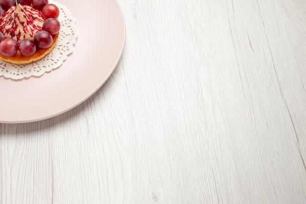 白い机の上のプレートの中にブドウが入った正面図の小さなケーキフルーツデザートケーキ