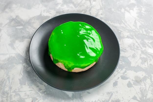 白い机の上に緑のアイシングと正面図の小さなケーキ