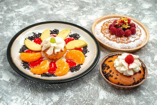 흰색 배경에 얇게 썬 과일과 파이가 있는 작은 케이크 달콤한 과일 케이크 쿠키 설탕 비스킷