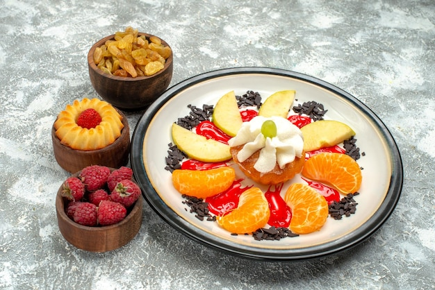 Vista frontale piccola torta con frutta a fette e uvetta su sfondo bianco dolce di frutta biscotto zucchero biscotto torta