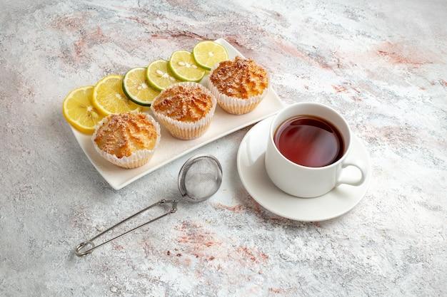 Вид спереди маленькие пирожные, запеченные и сладкие с ломтиками лимона и чашкой чая на белой поверхности, тесто для печенья, сахарное сладкое печенье