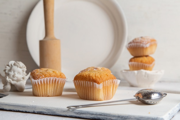 Front view of little cakes inside paper forms with sugar powder on the white desk