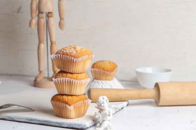 Front view of little cakes inside paper forms with sugar powder on the white surface