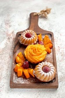 正面図小さなケーキ白い背景の上の果物とお茶のための完璧なデザートティーパイケーキデザート甘いクッキー