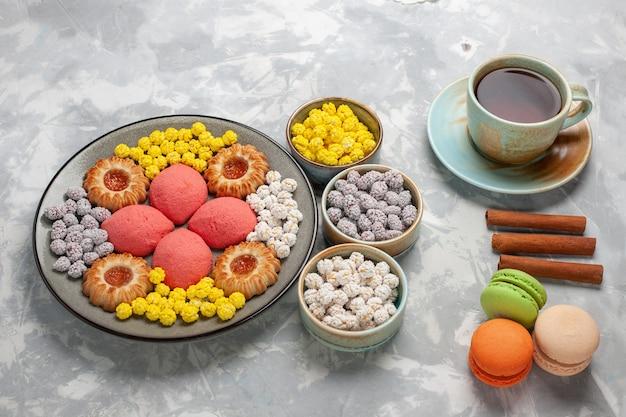 Vista frontale piccole torte con caramelle tazza di tè e biscotti sulla superficie bianca