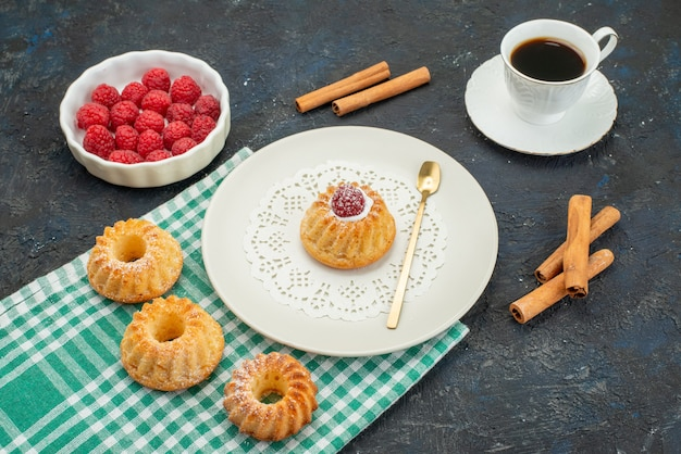 正面は暗い表面にコーヒーと一緒にシナモンと新鮮な赤いラズベリーと小さなケーキ
