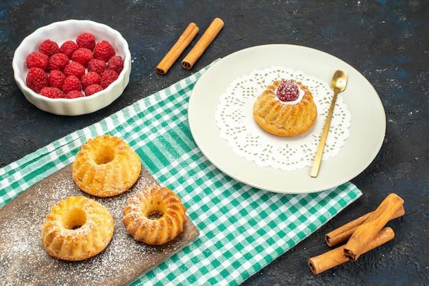 正面は暗い表面にシナモンと新鮮な赤いラズベリーと小さなケーキ