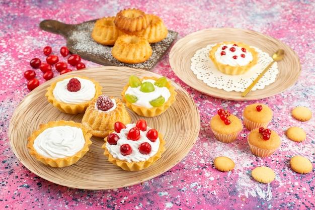 Vista frontale piccole torte con panna fresca e frutta sul biscotto di superficie brillante