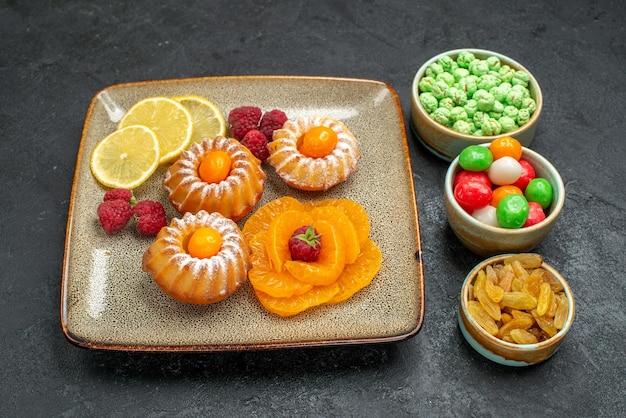 Вид спереди маленькие пирожные с дольками лимона, мандаринами и конфетами на темном пространстве