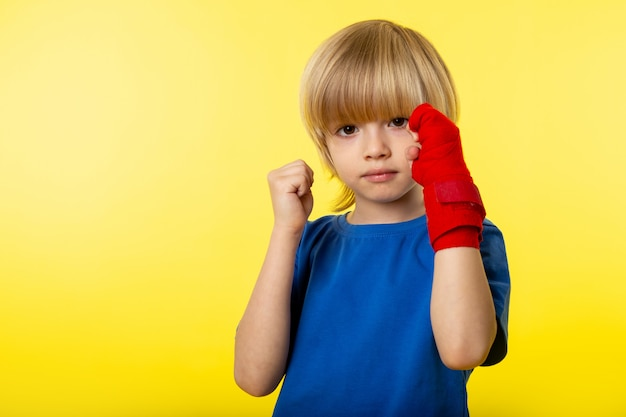 A front view little child boy posing boxing in blue t-shirt on the yellow wall