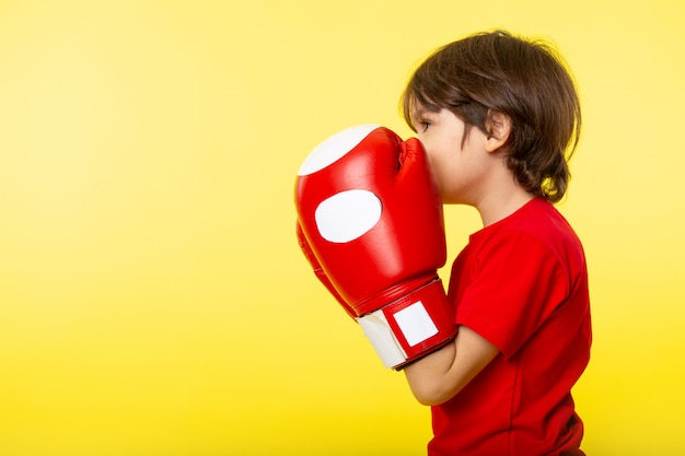 A front view little child in red t-shirt and red gloves on the yellow wall