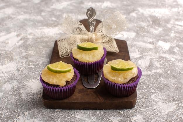 Вид спереди маленькие шоколадные пирожные с ломтиками лимона на сером письменном столе, печенье, печенье, сладкое тесто для выпечки