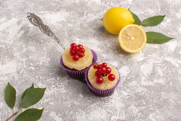 Вид спереди маленькие шоколадные пирожные с клюквой и лимоном на сером письменном столе, печенье, сладкое тесто для выпечки