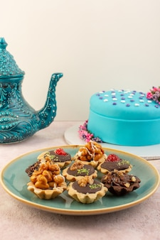 A front view little chocolate cakes inside plate with blue birthday cake on the pink desk