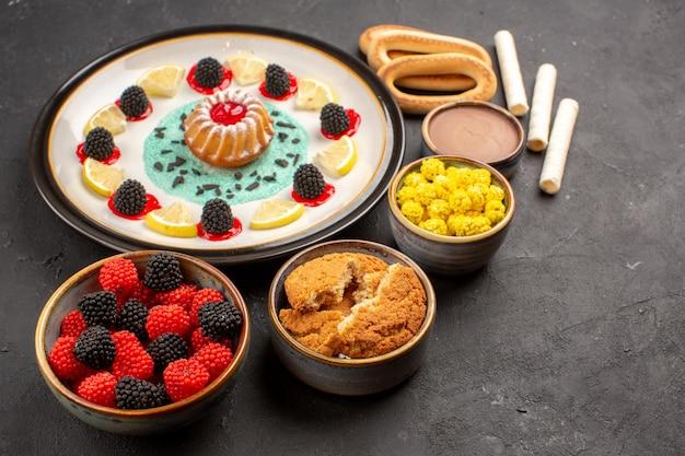 Vista frontale piccola torta di biscotti con fette di limone e caramelle su sfondo scuro torta biscotto frutta agrumi biscotto dolce