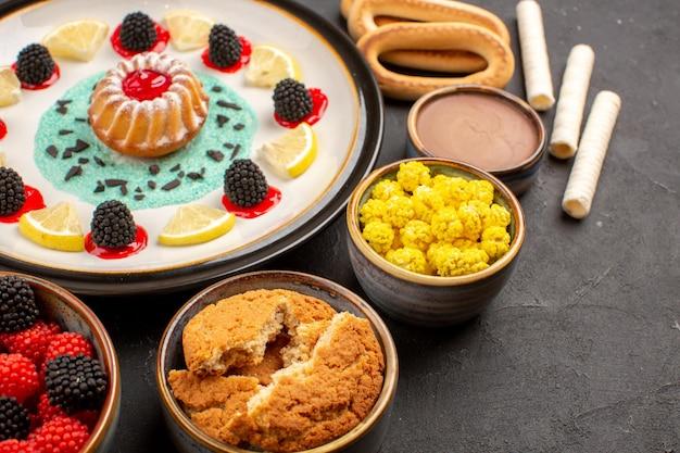 Vista frontale piccola torta di biscotti con fette di limone e caramelle su sfondo scuro torta biscotto frutta biscotti dolci agli agrumi