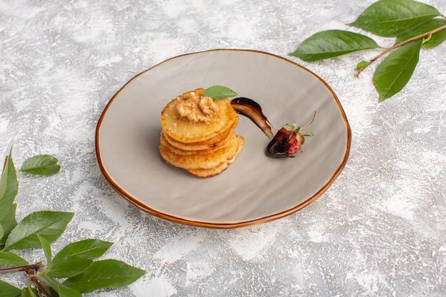 Вид спереди маленькое печенье внутри тарелки на светлом столе, выпечка из сладкого печенья с сахаром