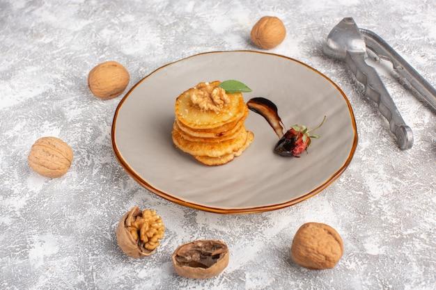 Вид спереди маленькое печенье с грецкими орехами на светлом столе, выпечка из сладкого бисквитного торта