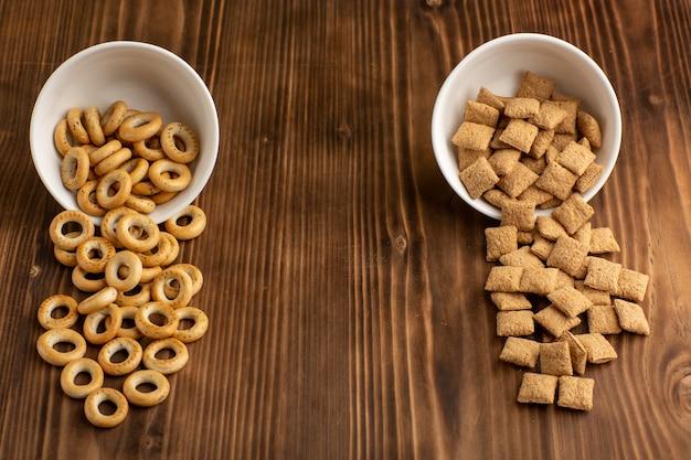 茶色の木製の机の上の小さなクッキーとクラッカーの正面図