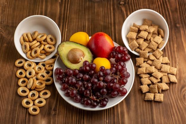 正面図茶色の木製の机の上の果物と小さなクッキーとクラッカー