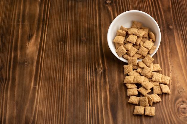 茶色の木製の机の上のプレート内の小さなクッキーの正面図