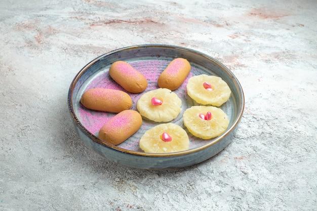 Вид спереди маленькое печенье с сушеными кольцами ананаса на белом пространстве