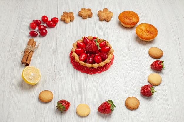 正面図白い机の上の果物とケーキと小さなクッキークッキービスケットスウィートティー