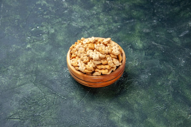 Vista frontale piccoli cracker all'interno del piatto sullo sfondo scuro spuntino croccante sale pane fette biscottate cibo cips colore