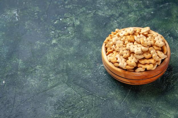 Vista frontale piccoli cracker all'interno del piatto su sfondo scuro spuntino croccante sale fette biscottate cibo cips colore